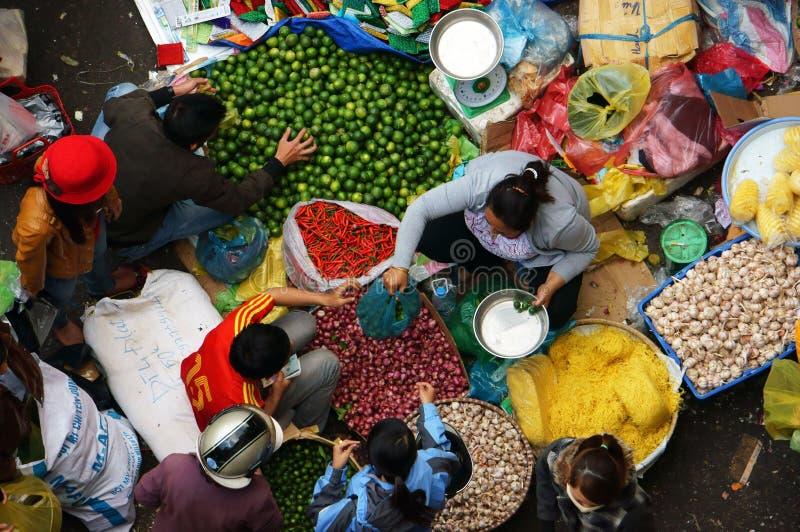 Ludzie sprzedają pikantność i kupują przy na wolnym powietrzu rynkiem. DA LAT, WIETNAM LUTY 8, 2013 obraz stock