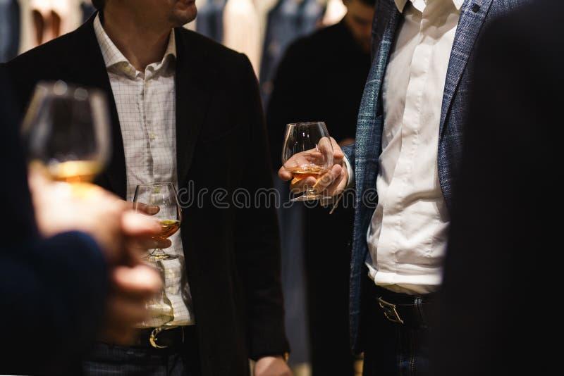 Ludzie stoi gawędzenie przy szkło degustacją i degustating szefa kuchni biznesowego gościa restauracji mienia wina i whisky karmo obraz stock