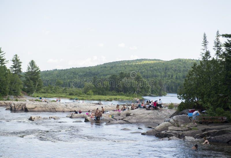 Ludzie sunbathe na skałach obok rzeki obrazy stock