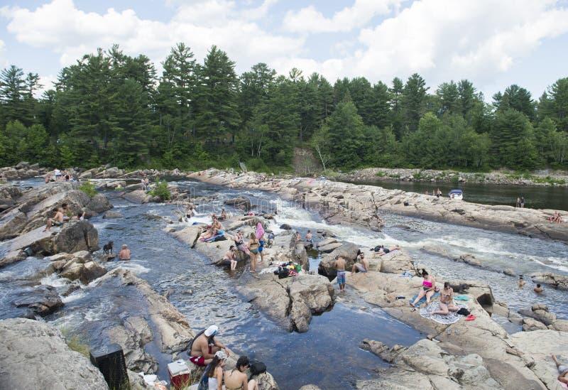 Ludzie sunbathe na skałach obok rzeki zdjęcia royalty free