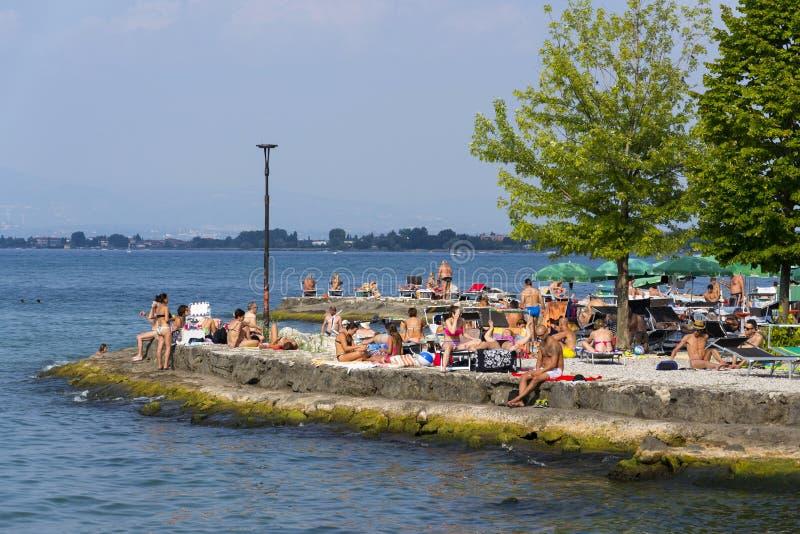 Ludzie sunbathing na plaży na 30 2016 w Desenzano Del Garda Lipu, Włochy obraz royalty free