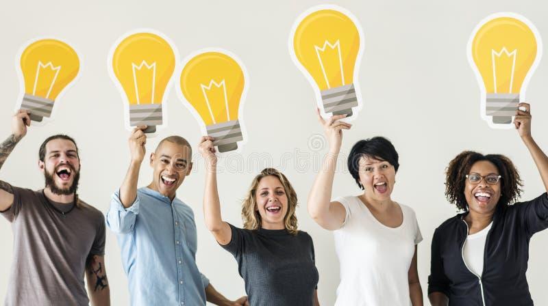 Ludzie trzyma lightbulb ikony wpólnie obraz stock