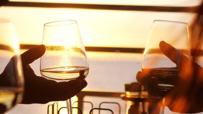 Ludzie trzyma szkło wino, robi grzance nad zmierzchem Przyjaciele pije białego wino, wznosi toast clink Przyjęcie outdoors zdjęcia stock