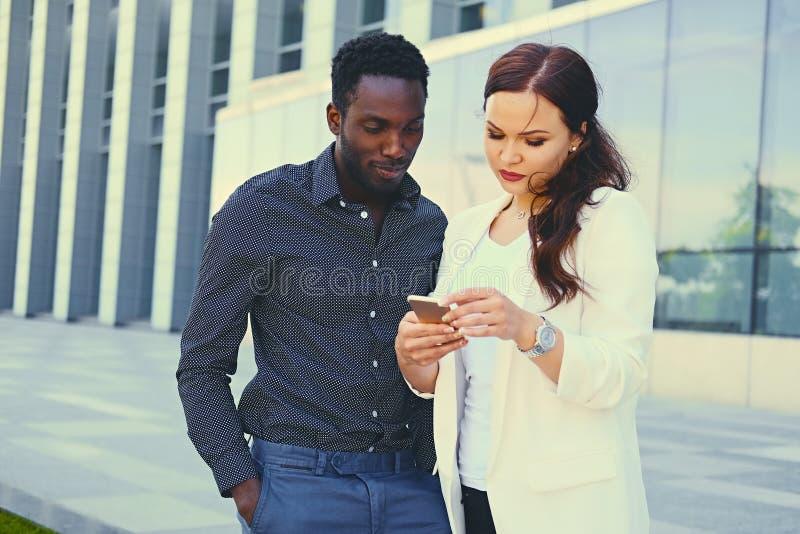 Ludzie używa smartphones nad nowożytnym budynkiem fotografia royalty free