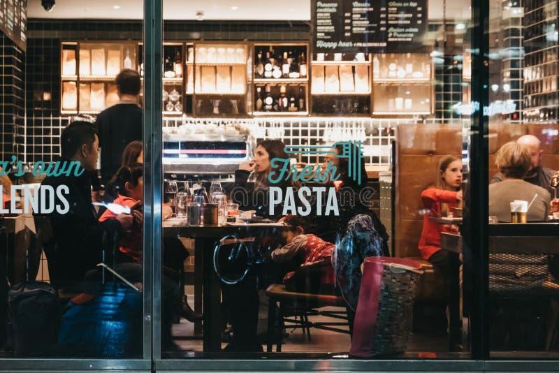 Ludzie wśrodku Włoskiej restauracji w Canary Wharf, Londyn, UK, widok przez okno z zewnątrz obrazy royalty free
