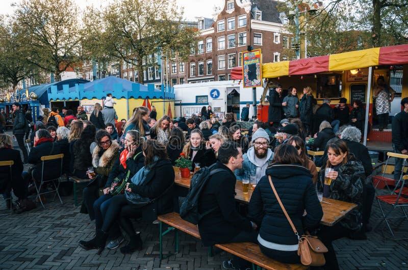 Ludzie w plenerowej kawiarni na Nieuwmarkt w Amsterdam, holandie obraz stock