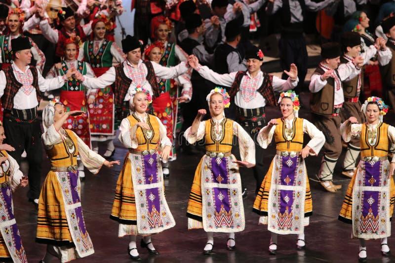 Ludzie w tradycyjnych folklor?w kostiumach wykonuj? ludowego tana Bu?garski Horo obraz stock