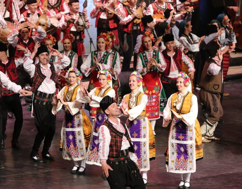 Ludzie w tradycyjnych folklor?w kostiumach wykonuj? ludowego tana Bu?garski Horo zdjęcie stock