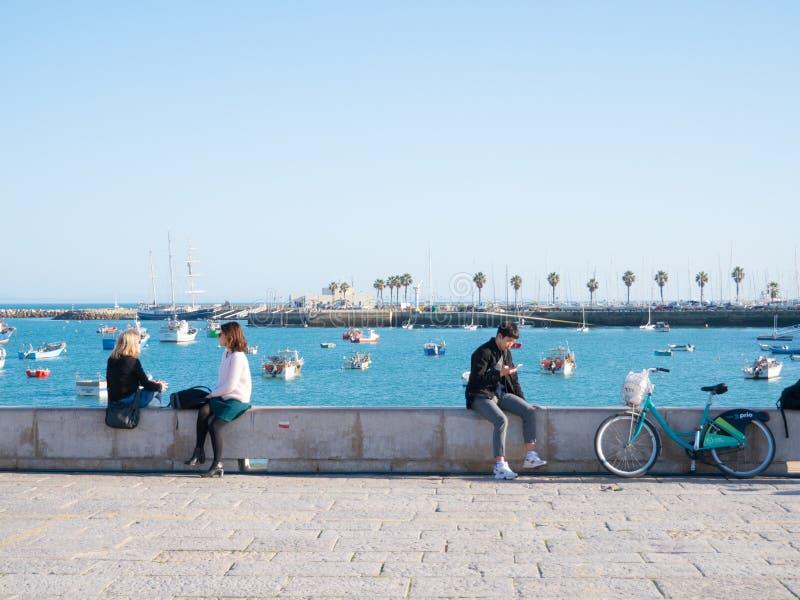 Ludzie wakling na nadbrzeża parapet i patrzeje most w Lisbon i morze zdjęcia stock
