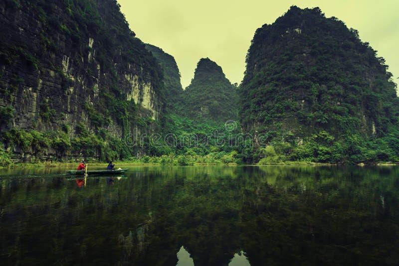 Ludzie wiosłują na jasnej rzece która może widzieć pod trawą fotografia stock