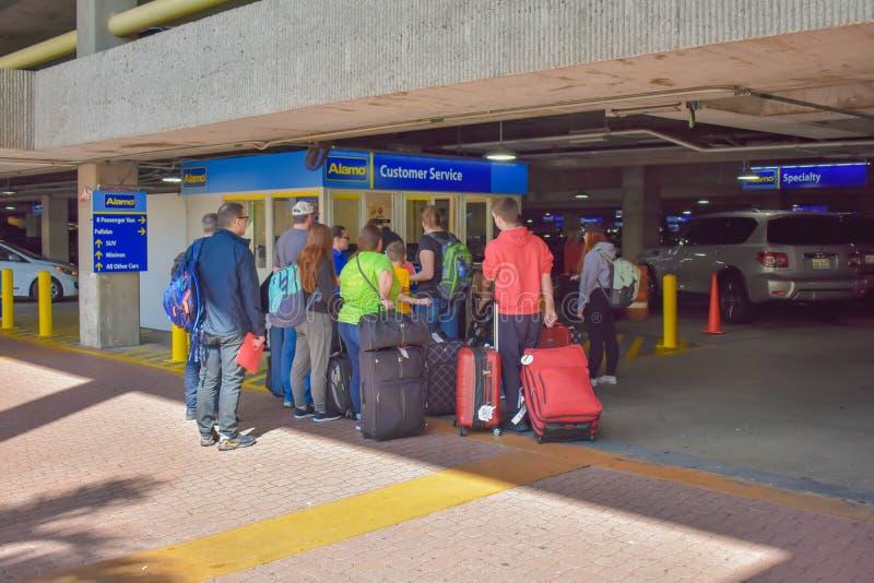 Ludzie z bagażu wchodzić do czekaniem wewnątrz dzierżawią samochód przy Orlando lotniskiem międzynarodowym zdjęcia stock
