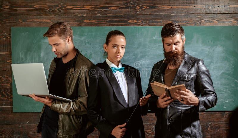 Ludzie z laptopu ksi??kowym stojakiem w szkolnej sali lekcyjnej Nauczyciele Brodatego mężczyzny męska dziewczyna i przystojna fac obrazy royalty free