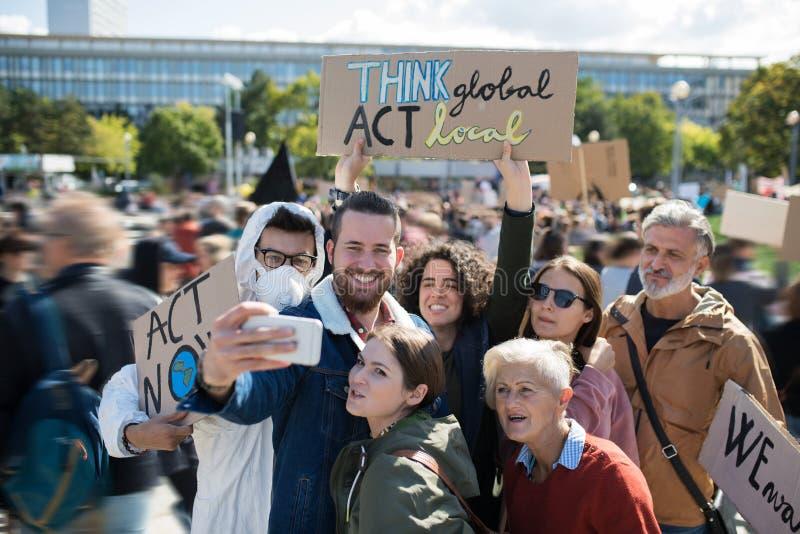 Ludzie z plakatami i plakatami o globalnym strajku na rzecz zmian klimatycznych, zabierający selfie obrazy royalty free