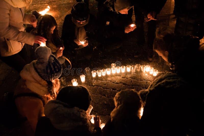 Ludzie zaświecają małe świeczki na ulicie w zmroku zdjęcie stock
