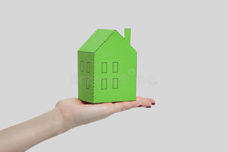 Ludzka kobiety ręka trzyma zielonego papieru domu modela i pokazuje W obrazy stock