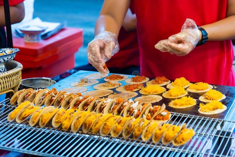 Ludzka ręka gotuje świeżego Tajlandzkiego crispy blin Buang lub Kanom obrazy royalty free