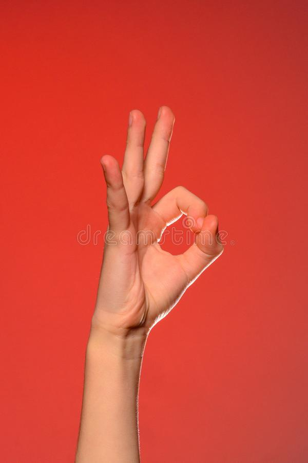 Ludzka ręka pokazuje znaka ok symbolizuje pozytyw, odizolowywającego na czerwonym tle obrazy stock