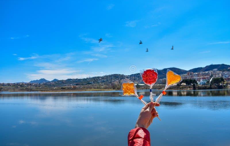 Ludzka ręka trzyma kolorowych lizaki przeciw sztucznemu jezioru fotografia stock