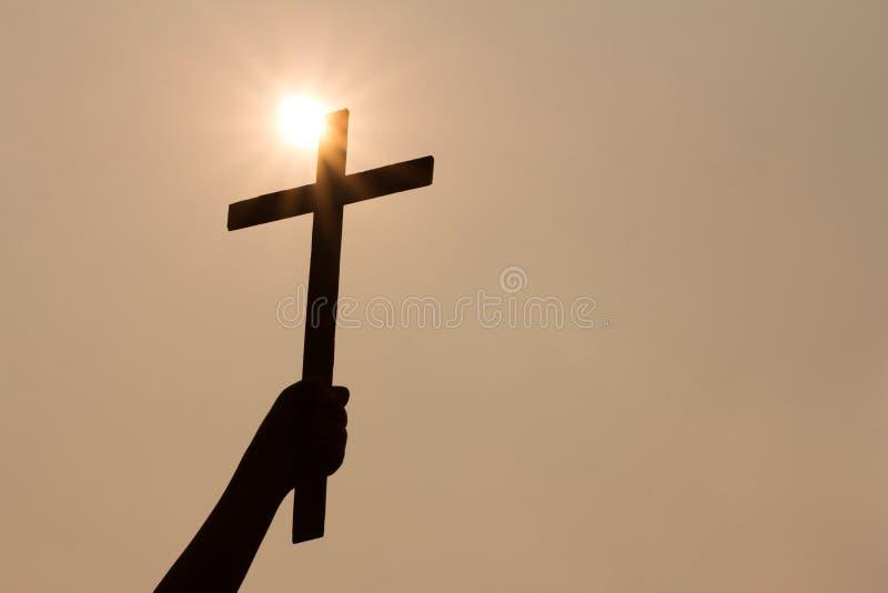 Ludzka ręka trzyma krzyż tło jest wschodem słońca zdjęcie stock