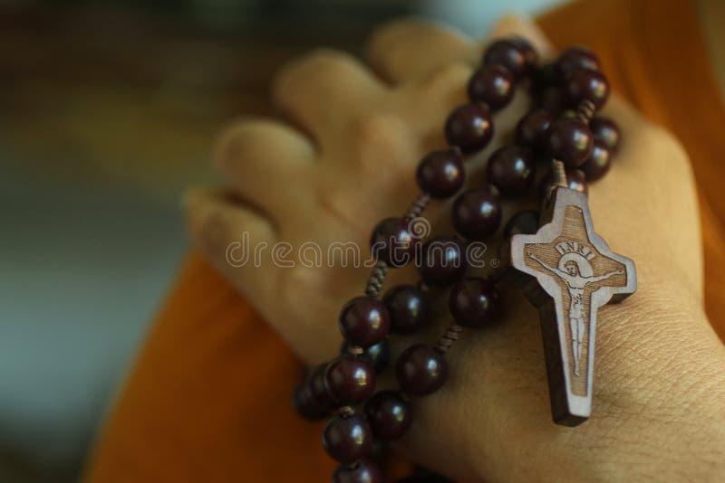 Ludzka ręka trzyma różana na naramiennym zbliżeniu Młodzieżowy młody człowiek trzyma różana z jezus chrystus krzyżem wręcza modle obraz stock