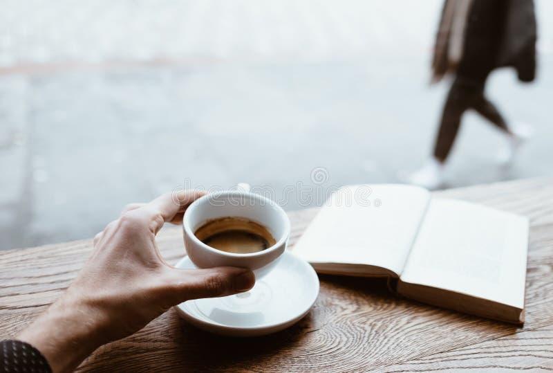 Ludzka ręka trzymająca czarną kawę na spodku z książką na tle na drewnianym stole obok dużego okna kawiarni i fotografia stock