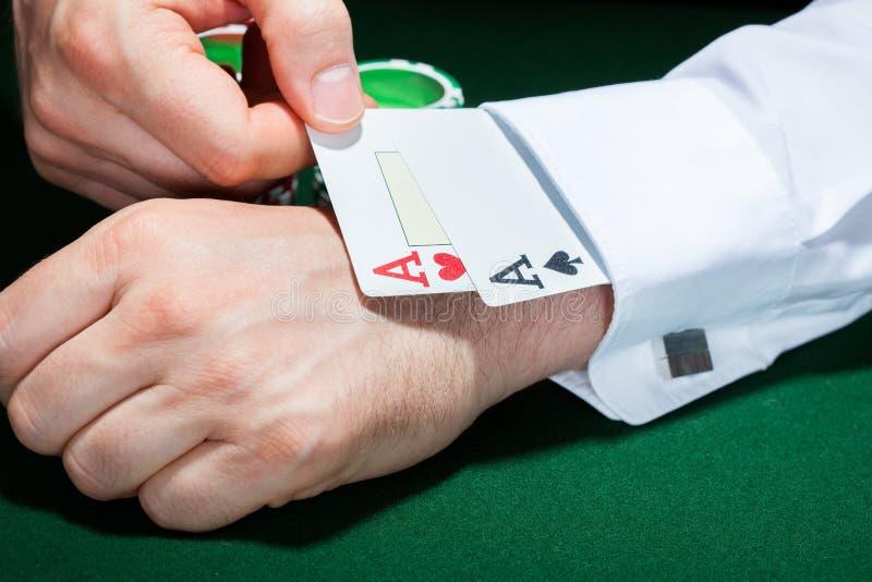Ludzka ręka z karta do gry w rękawie obraz stock