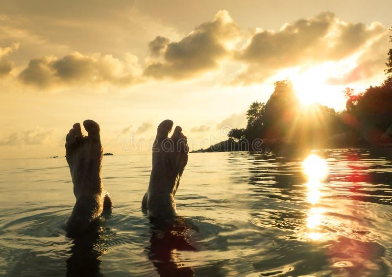 Ludzki barefeet przy plażą na zmierzchu w Koh Lipe fotografia stock