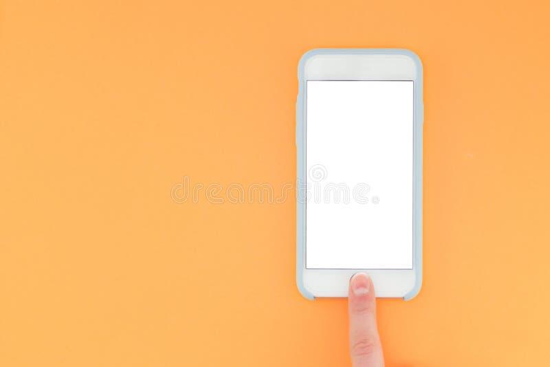 Ludzki palec otwiera smartphone na pomarańczowym tle Mieszkanie nieatutowy obraz stock
