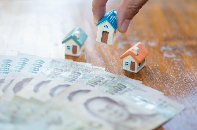 Ludzki ręki kładzenia domu model na banknotach, planistycznym oszczędzanie pieniądze monety kupować domowego pojęcie, hipotece i  obrazy royalty free
