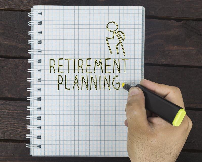Ludzki ręki writing emerytura planowanie w ślimakowatym notepad Modny ciemny drewniany tło obraz royalty free