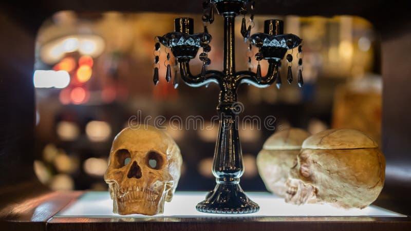 Ludzkie czaszki i szkło stół obrazy stock