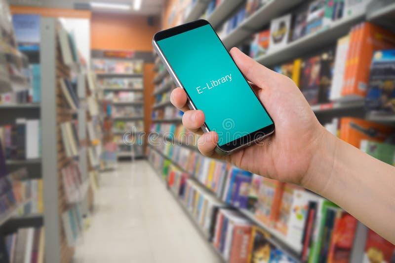 Ludzkiego prawa ręka chwyta mądrze telefon, pastylka, telefon komórkowy z wirtualną app biblioteką na rozmytym półka na książki w obrazy royalty free