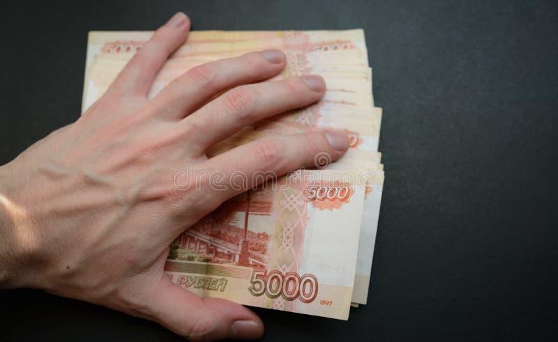 Ludzkiej ręki pokrywy thousandth banknoty fotografia stock