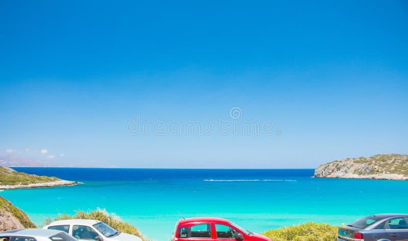 Lue och turkos som är beachfront med bilparkering Voulisma strand nära till Agios Nikolaos royaltyfri bild