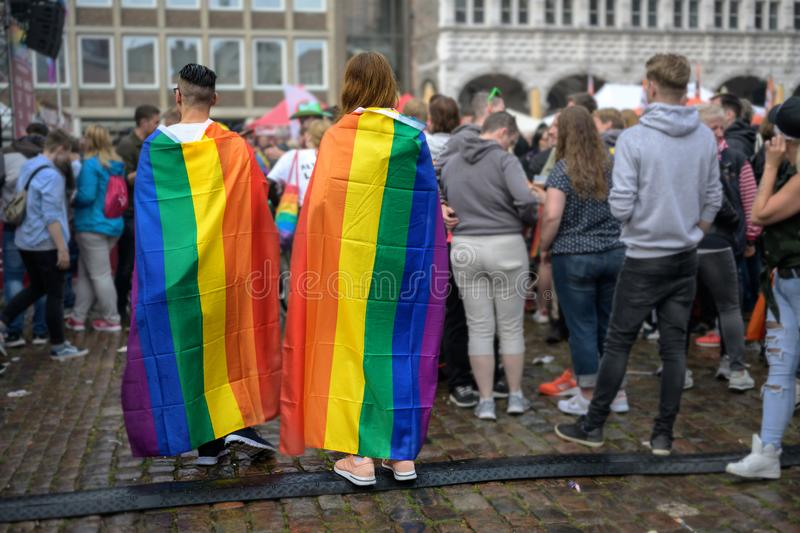 LUEBECK, GERMANY, AUGUST 17, 2019: two young people from behind are wearing rainbow flags as capes, colorful eye-catcher in the royalty free stock image