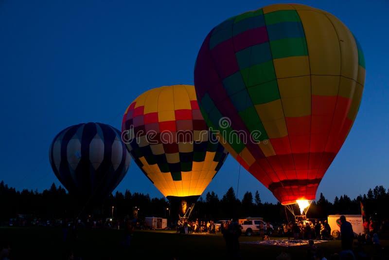 Lueur chaude de nuit de ballons à air dans la courbure Orégon images stock