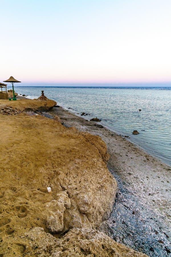 Lueur de coucher du soleil, parasols sur la belle plage sablonneuse images stock
