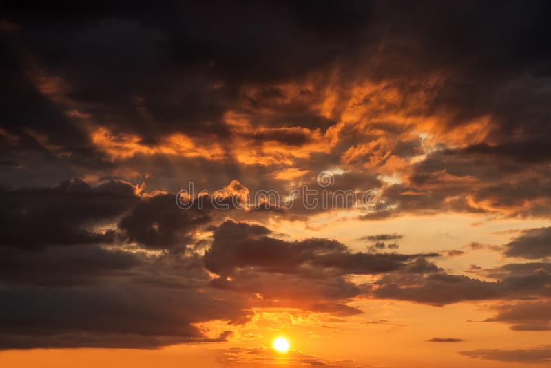 Lueur de coucher du soleil sur un ciel nuageux avec le soleil et de rayons derrière les nuages photo stock
