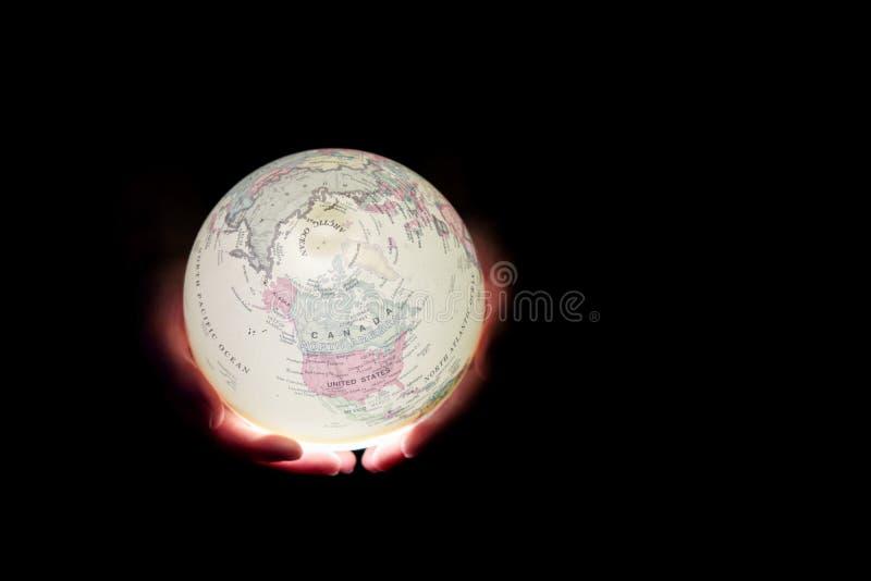 Lueur de globe dans des mains Jour de terre photo stock