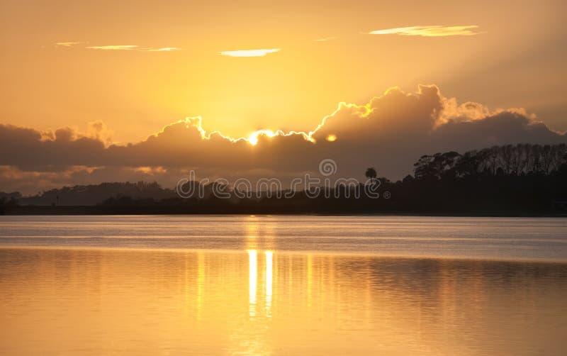 Lueur de Soleil Levant derrière des nuages à travers la baie images libres de droits