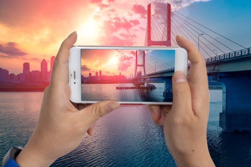 Lueur-utilisation de coucher du soleil un téléphone portable de prendre des photos images stock