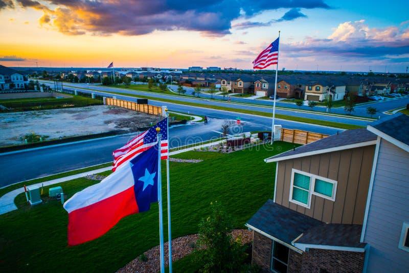 Luft- Brummenansicht nahe bei der amerikanischen Flagge und Texas Flag, die hoch über moderne Tag-Subrub-Entwicklungen fliegen lizenzfreie stockbilder