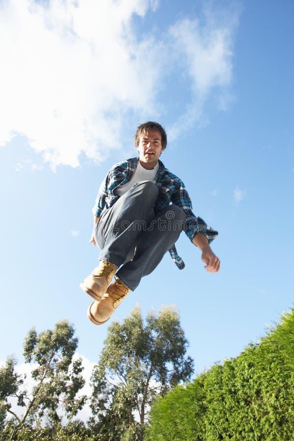 luft fångat hoppa mitt- trampolinebarn för man fotografering för bildbyråer