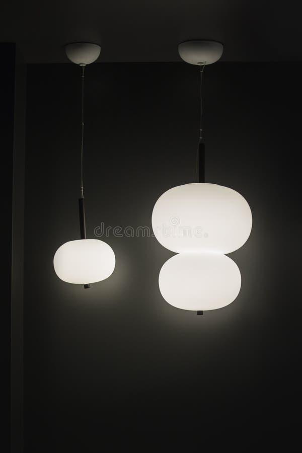 Luft, Licht, runde Lampen, hängende Leuchter in der skandinavischen unbedeutenden Art auf einem schwarzen Hintergrund lizenzfreies stockfoto