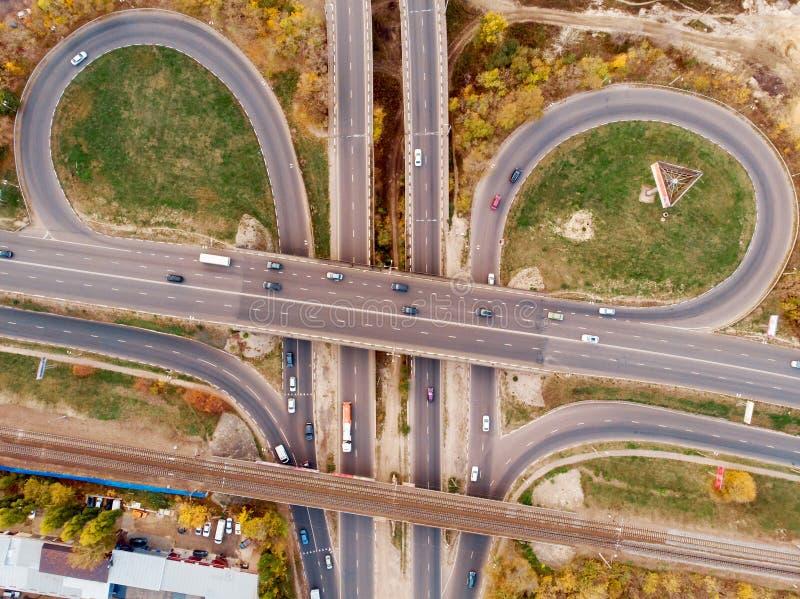 Luft- oder Draufsicht der Transportkreuzung, der Asphaltstraßen mit Kreuzung und der Kreisschnitte, Stadtverkehrsautos von oben stockfotos