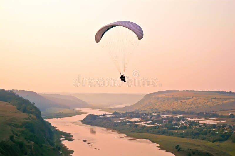 Luftabenteuergleitschirmfliegen über Fluss lizenzfreies stockbild