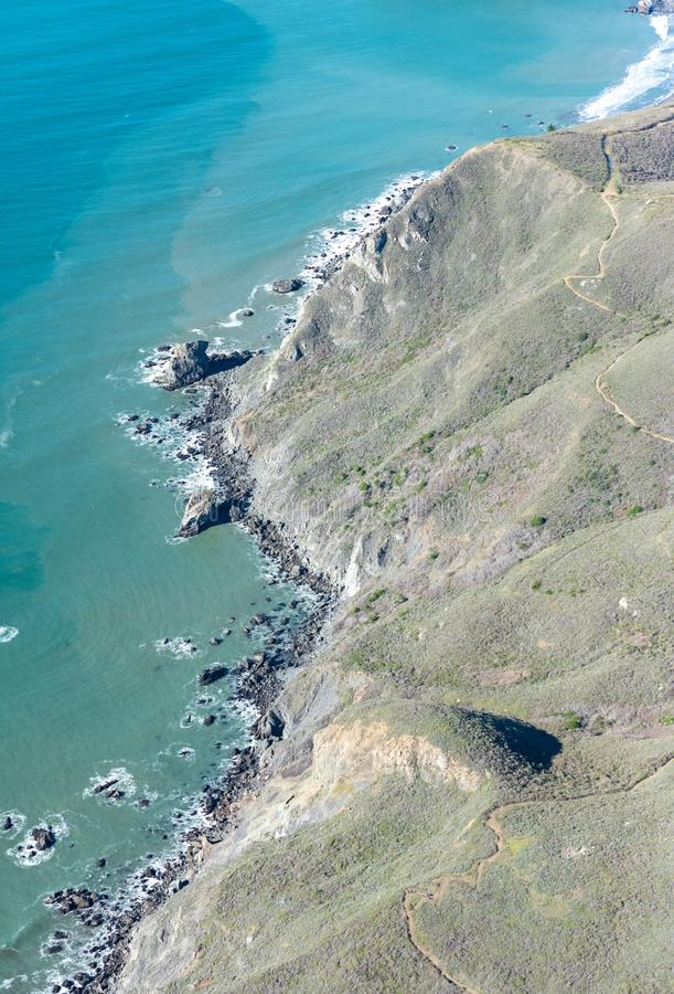 Luftaufnahme der pazifischen Küstenlinie mit Hügeln und Spuren und blauer Ozean lizenzfreie stockfotografie