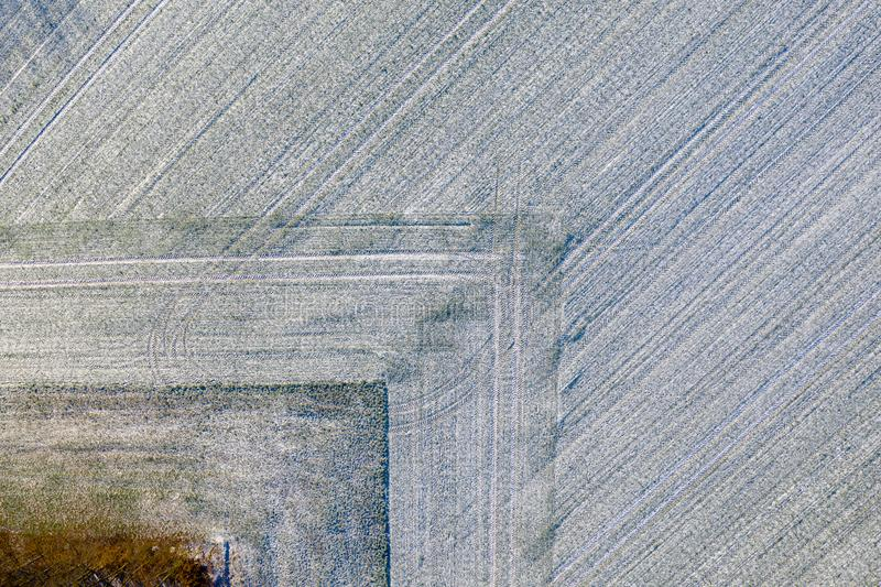 Luftaufnahme eines Feldes mit einer Dünnschicht des Schnees sorgfältig gepflogen in einer geometrisch rechteckigen Form lizenzfreie stockbilder