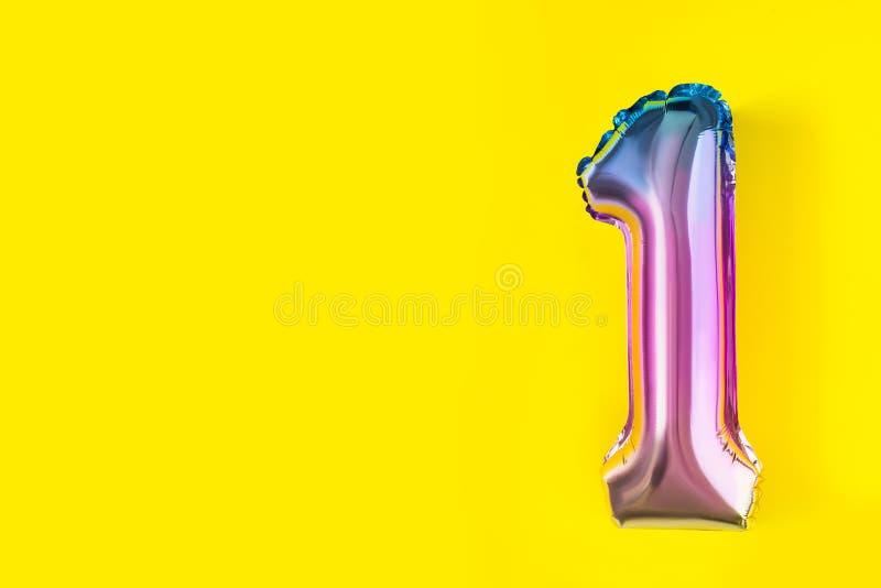 Luftballonger av formad folie för nummer ett på pastellfärgad gul bakgrund Minimalistic sammansättning av den metalliska ballonge royaltyfri fotografi