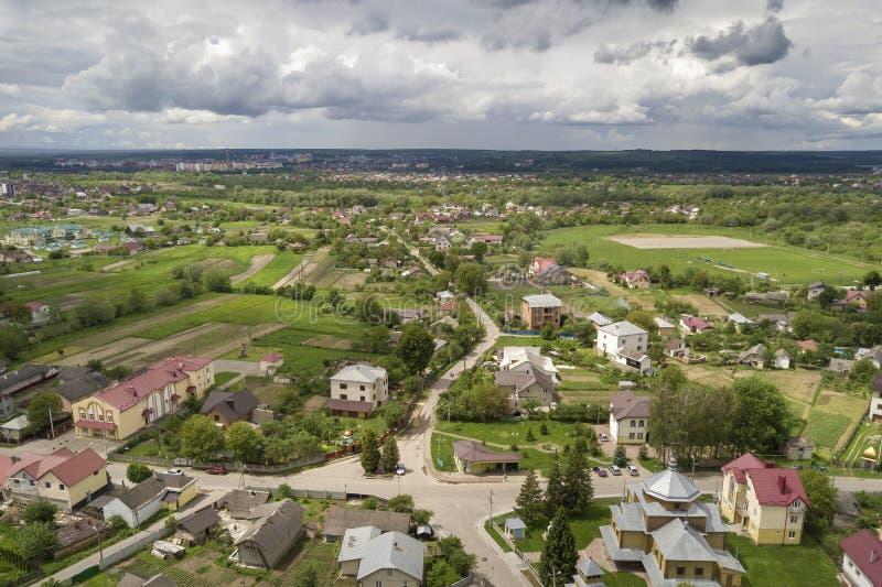 Luftbild der Stadt oder des Dorfes mit Reihen von Gebäuden und kurvigen Straßen zwischen grünen Feldern im Sommer Landschaft von lizenzfreie stockfotografie
